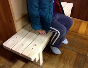 ヒノキのベンチに座る幼児